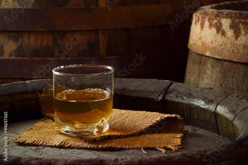 Fotografie, Obraz  glass of brandy in the cellar with old barrels stacked