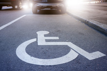 Handicap Symbol On Road, Traffic And Pedestrians In Background
