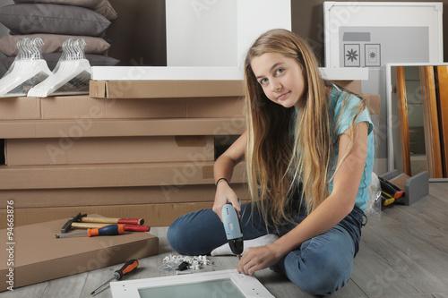 Fototapety, obrazy: Jeune fille assemble un meuble