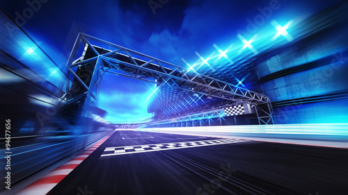 Photo Stands Motor sports finish gate on racetrack stadium and spotlights in motion blur