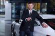 Autoverkäufer überreicht lässig den Schlüssel fürs Auto