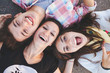 canvas print picture - Closeup of three best friends lying down and laughing. Teenage people wearing casual clothes smiling. Top view