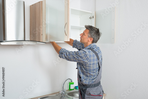 Fotografie, Tablou  Serviceman Fixing Cabinet With Screwdriver In Kitchen