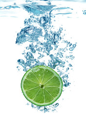 Naklejka Lime slice dropped in a water above white background