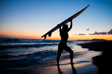 Young female surfer on beach in sunset