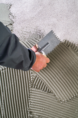 Photo  Construction notched trowel with grey cement mortar for tiles wo