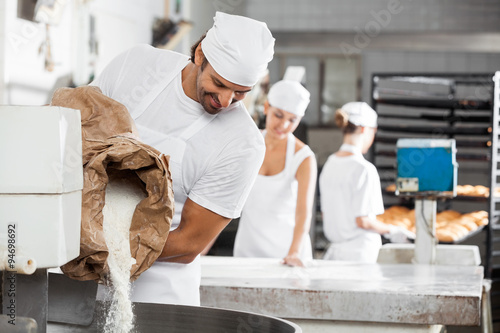 Tuinposter Bakkerij Male Baker Pouring Flour In Kneading Machine
