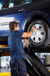 Mechanic Refilling Car Tire At Garage