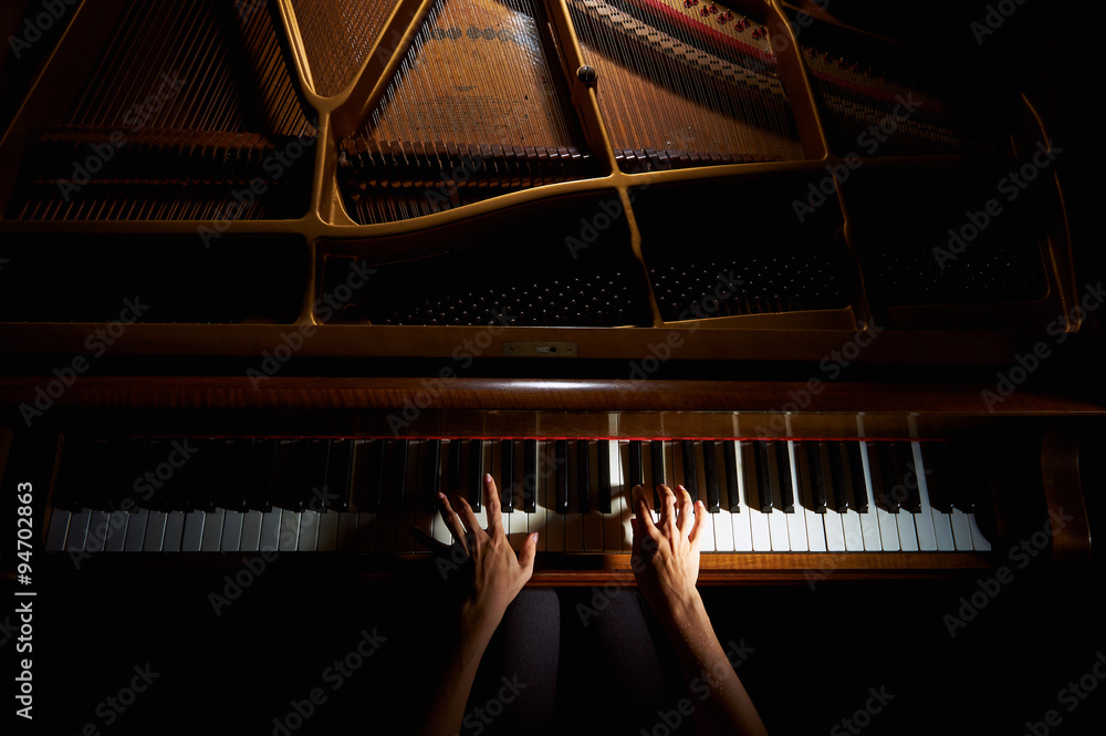 Fototapeta Woman's hands on the keyboard of the piano in night closeup