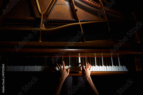 Fotografie, Obraz  Woman's hands on the keyboard of the piano in night closeup