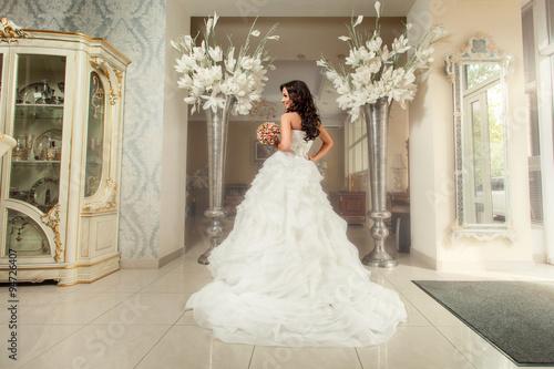 Fotografie, Obraz  Bride in white wedding dress. Standing back to camera.