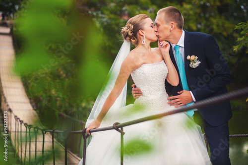 Photo Bride with groom on the bridge in forest