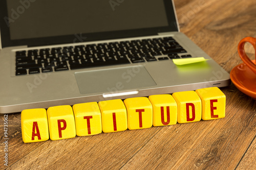 Aptitude written on a wooden cube in front of a laptop Wallpaper Mural