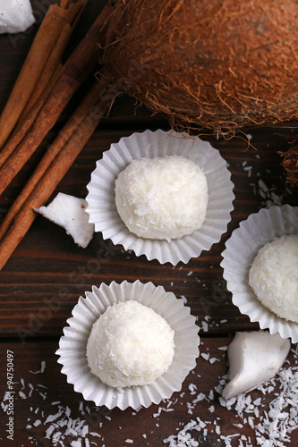 Candies in coconut flakes and fresh coconut on dark wooden