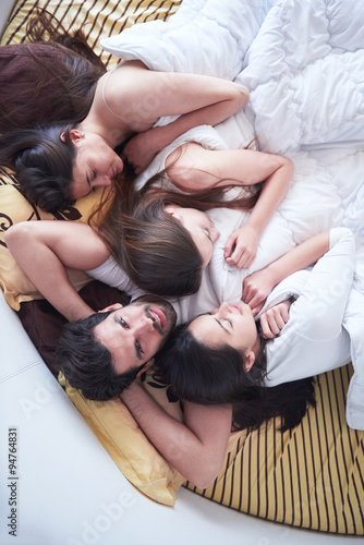 Foto  handsome man in bed with three beautiful woman