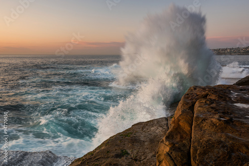 Foto auf Gartenposter Wasser Sunrise seascape with unrest sea and blue water and with sky lit orange rocks and big crashing wave