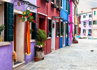 Plakat street with multi-colored bright houses on Burano's island, Venice, Italy