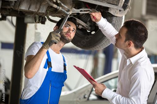 assessor and repair man examine car Canvas Print