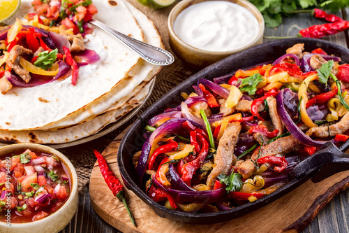 Fényképezés  Pork fajitas with onions and colored pepper, served with tortill