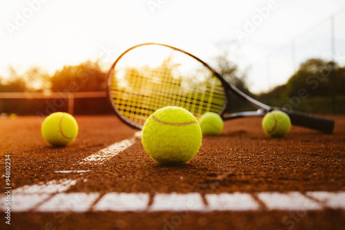 Tennis balls with racket on clay court Poster
