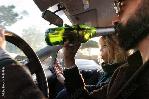 Fototapeta  dangerous driving drinking alcohol in car and woman looks scared
