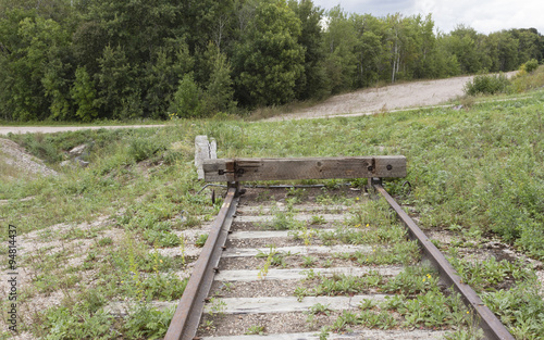 In de dag Kanaal horizontal image of the end of a railroad track going no where with green grass all around.