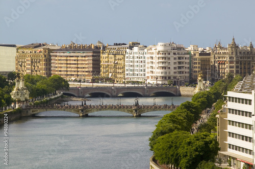 Photo  Apartment buildings line the river of Urumea beyond the Maria Cristina Bridge in