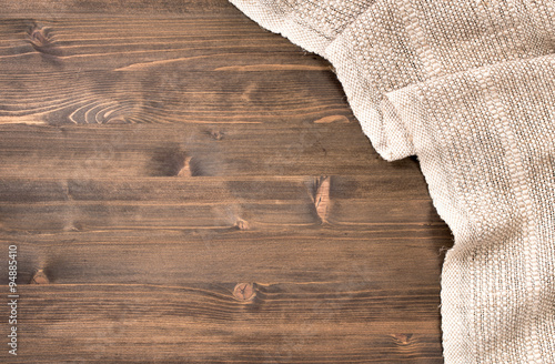 Fototapeta Gray handmade tablecloth from right side of wooden table