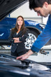 Businesswoman waits for a mechanic to fix her car