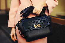 Elegant Outfit. Closeup Of Black Leather Bag Handbag In Hand Of Stylish Woman. Fashionable Girl On The Street. Female Fashion. Toned
