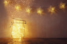 Low Key And Vintage Filtered Image Of Fairy Lights In Mason Jar With. Selective Focus. Glitter Overlay