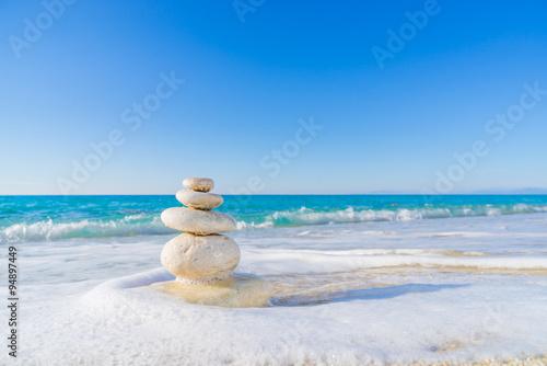 Acrylic Prints Stones in Sand Stones pyramid on sand symbolizing zen, harmony, balance. Ocean
