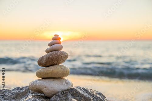 Fotobehang Stenen in het Zand Stones pyramid on sand symbolizing zen, harmony, balance. Ocean