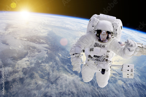 Photo  Astronaut in Space, in background our earth an the sun - Elements of this image