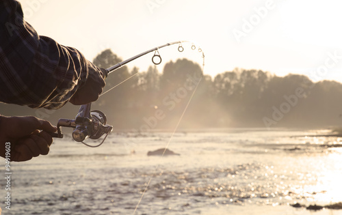 the fisherman is fishing on a river in the early morning. Fotobehang