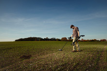 Exploring Autumn Field With Metal Detector