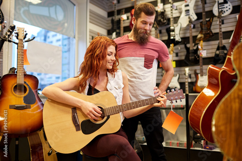 Spoed Foto op Canvas Muziekwinkel couple of musicians with guitar at music store