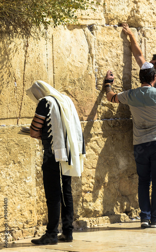 Fotobehang Midden Oosten Unidentified jewish worshiper in tallith and tefillin praying at the Wailing Wall an important jewish religious site