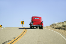 A Restored Bright Red Roadster Hotrod Pickup Truck, Mid-30's, Drives Rural Highway In Kern County Near Lockwood Valley, CA