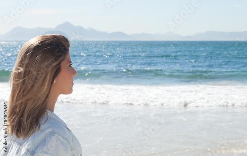 Valokuva  Frau mit blonden Haaren schaut auf das Meer