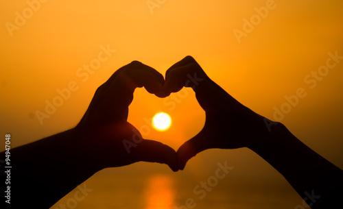 Fotografie, Obraz  hand making heart shape over sunset