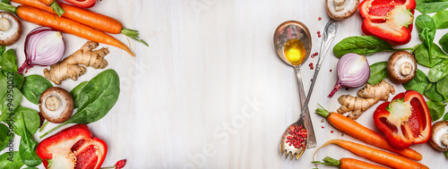 Spoed Fotobehang Eten Organic vegetables assorted with cooking spoons and oil on white wooden background