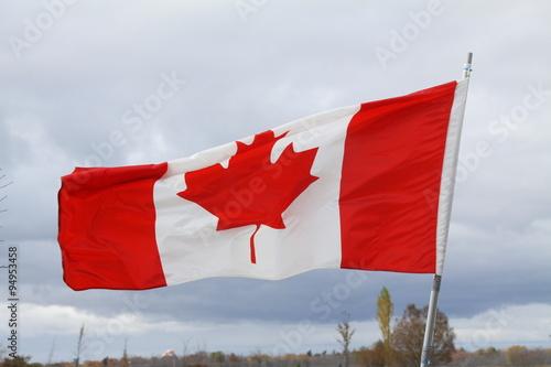 Spoed Foto op Canvas Canada Flag of Canada gently waving in a light breeze against clouds and blue sky.