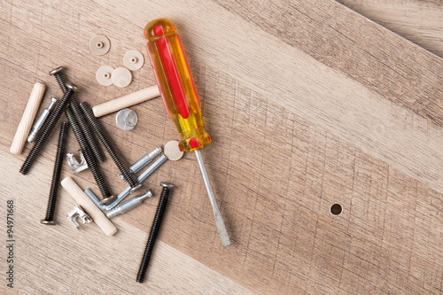 Fotografie, Tablou  Screwdriver and Hardware Scattered on Wood Planks