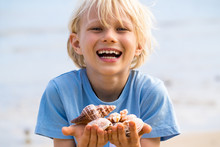 Happy Smiling Cute Child On Holiday With Collection Of Shells At Beach