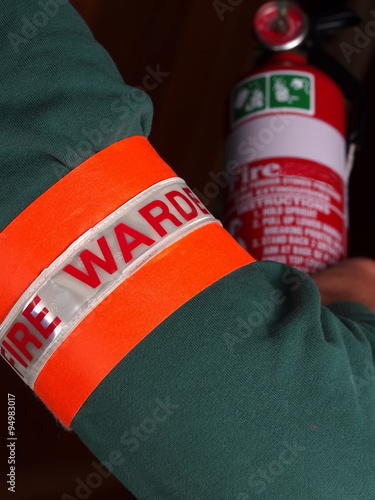 Photo Fire warden with a reflective high visibility identification patch holding a fir