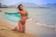 closeup brunette girl in bikini stands on knees on wet sand