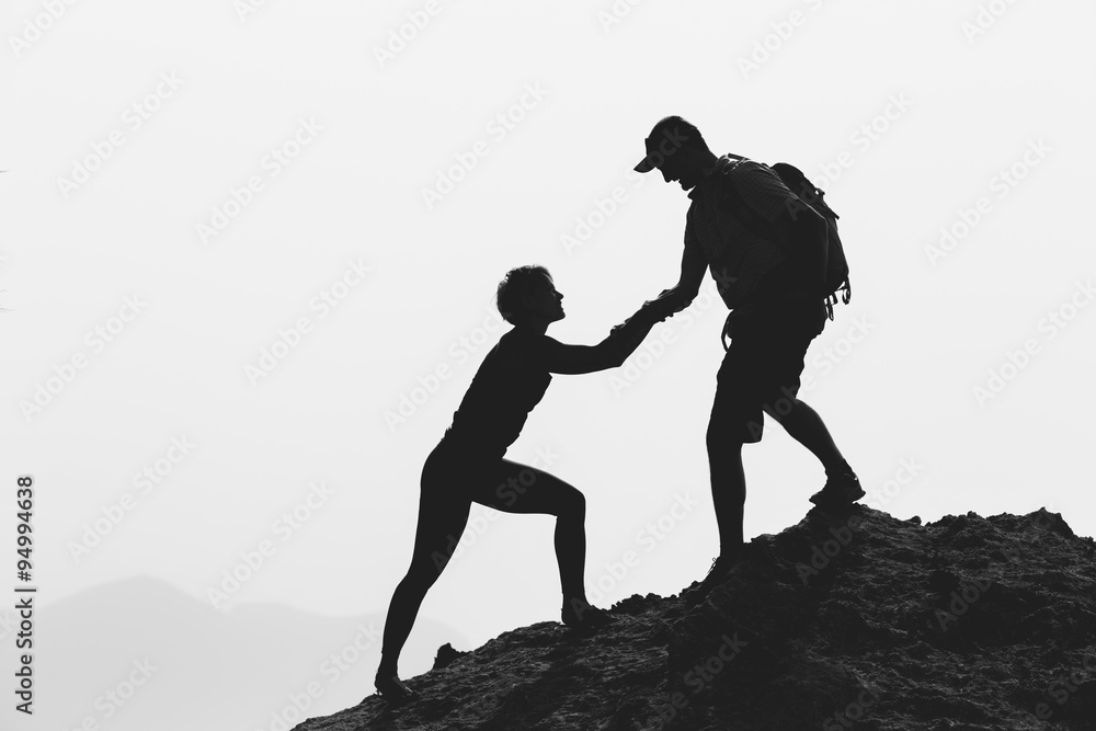 Fototapeta Teamwork couple helping hand hiking and climbing
