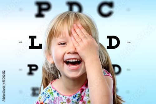 Cuadros en Lienzo Girl having fun at vision test.