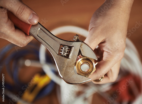 Close-up of plumber hands screwing nut of pipe with wrench over plumbing tools background Fototapeta